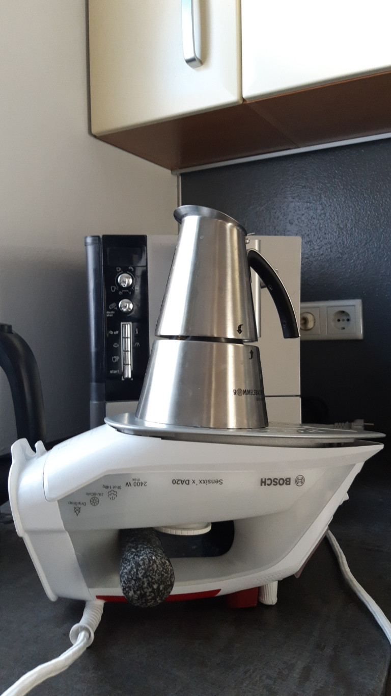An electric pressing iron turned upside down to heat an italian espresso cooking can.